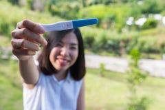 Krótkiego włosy młoda kobieta uśmiecha się ciążowego test i pokazuje Zdjęcie Royalty Free