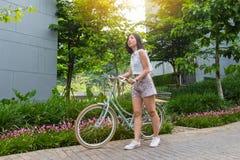 Krótkiego włosy młoda kobieta z jej bicyklem Fotografia Royalty Free