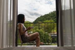 Krótkiego włosy młodej kobiety obsiadanie przy balkonem Obraz Royalty Free