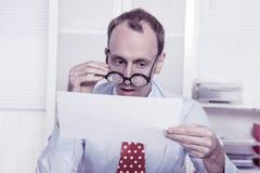 Krótkowzroczny przy pracą - łysienie biznesmen patrzeje przez glas Obrazy Stock