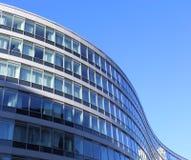 Krökt facde av modern himmel för solig dag för byggnad blå arkivfoto
