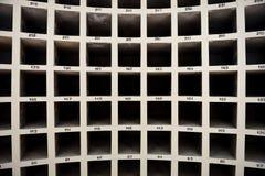 Krökt formad vägg med rader och modeller av numrerade fyrkantiga rum arkivfoton