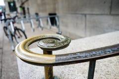 Krökt metallledstång på en utomhus- trappuppgång arkivbild