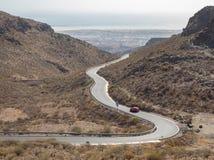 Krökt slingrig väg med en röd bil i bergen i Gran Canaria royaltyfri foto