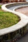 Krökt stenvägg i formen av ett S royaltyfri foto