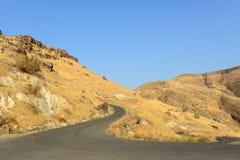 Krökt svart väg i gula kullar Royaltyfri Fotografi