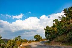 Krökt väg i stigande över de vita molnen och den blåa himlen arkivbilder