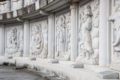 Krökt vägg och buddistisk marmorlättnad av buddism arkivbilder