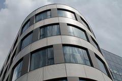 Krökt yttersida för exponeringsglas och för stål av en i stadens centrum kontorsbyggnad Arkivbild