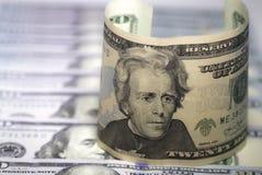 Krökta tjugo oss dollarsedelanseende på rad av hundra oss bakgrund för dollarräkningar Arkivfoto