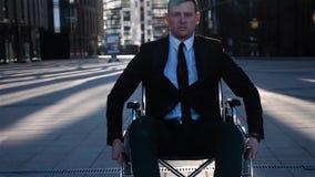 Krüppelgeschäftsmannbewegung im Rollstuhl auf nahem Geschäftszentrum der Kamera im Freien stock video footage