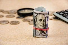 Kręceni dolary na tle monety, magnifier i kalkulator, fotografia stock