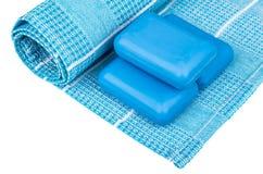 Kręcony błękitny ręcznik i kawałki mydło odizolowywający na bielu Zdjęcie Stock