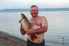 Krępy mężczyzna z dużym karpiem Khakassia Fotografia Royalty Free