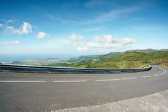 Kręcenie halna autostrada z niebieskim niebem i morze na tle Curvy droga przez trawiastych wzgórzy z widokiem Fotografia Royalty Free