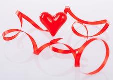 Kręcony czerwony faborek i ceramiczny serce Zdjęcie Stock