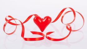 Kręcony czerwony faborek i ceramiczny serce Obraz Royalty Free