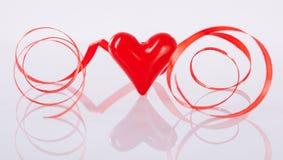 Kręcony czerwony faborek i ceramiczny serce Fotografia Stock