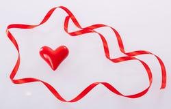 Kręcony czerwony faborek i ceramiczny serce Zdjęcia Royalty Free