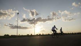 Krańcowi chłodno rowerzyści w szkoleniu robi w powietrzu obracają ćwiczy niebezpiecznych ruchy na bicyklach na biegowym śladzie i zdjęcie wideo