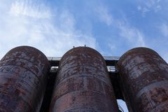 Krańcowy oddolny widok trzy wielkiego metalu zbiornika przeciw niebieskiemu niebu zdjęcie stock