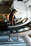 Köra på trampkvarnen i idrottshall- eller konditionklubban - sexig svart kvinna som övar för att vinna mer som är färdiga Royaltyfri Fotografi