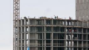 Kraan bij bouw van de bouwwerf de woonwoonwijk in de stad, aannemers het werken stock footage