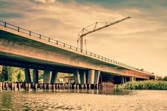 Kraan bij een brugbouw Stock Afbeeldingen