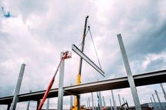 Kraan die concreet kader, shutterings en zware geprefabriceerde concrete componenten opheffen bij bouwwerf stock fotografie