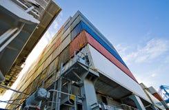 Kraan die container verminderen aan stapel containers Stock Afbeeldingen
