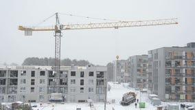 Kraan die het concrete deel en de arbeiders van het blokhuis in sneeuwstorm opheffen stock video