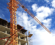 Kraan en arbeiders bij bouwwerf tegen blauwe hemel Royalty-vrije Stock Afbeeldingen