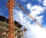 Kraan en arbeiders bij bouwwerf tegen blauwe hemel Royalty-vrije Stock Fotografie