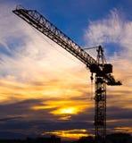Kraan tegen de zonsondergang met oranje wolken wordt gesilhouetteerd die Royalty-vrije Stock Foto