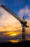 Kraan tegen de zonsondergang met oranje wolken wordt gesilhouetteerd die Stock Foto