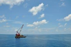 Kraanaak die zware lading of zware lift in de zeeolie en gasindustrie opheffen Grote boot die voor lift het door buizen leiden we Stock Foto