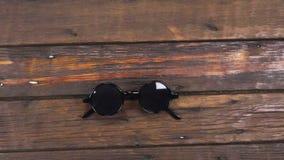 Kraancamera, die retro zonnebril die op een mooi, oud houten bureau met exemplaarruimte liggen zich omhoog bewegen stock videobeelden