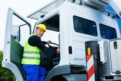 Kraanmachinist het drijven met vrachtwagen van bouwwerf Stock Foto's
