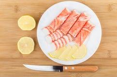 Krabbapinnar, kniv och stycken av citronen i den vita plattan Arkivbild