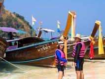 KRABI, ТАИЛАНД - 24-ое апреля 2016: Турист идя на спасательные жилеты пляжа нося в мелководье с длинными шлюпками и островом Tup Стоковые Фотографии RF