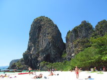 Krabi Beaches and Islands Thailand, limestone rock formations. Beautiful white sand beach, palm trees, blue water and clear blue sky on a sunny day. People Stock Photos