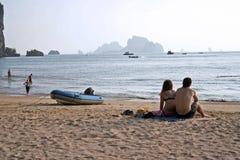Krabi couple ao nang beach thailand. Tourist couple sitting on ao nang beach in krabi thailand looking at karst islands in the andaman sea Stock Photo