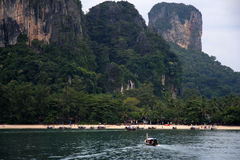 Krabi karst longtail boat thailand. Longtail boat steers toward railay beach below stunning karst landscape , krabi, southern thailand Stock Photos