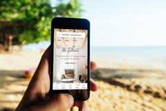 KRABI, TAILÂNDIA - 6 DE MARÇO DE 2018: Close up da tela do iPhone com o AirBNB MAIS Startscreen em uma praia Imagens de Stock Royalty Free