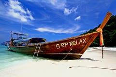 Krabi Tajlandia, Kwiecień, - 10, 2012: Duży długiego ogonu łódkowaty parking na białej piasek plaży z niebieskim niebem zdjęcia stock