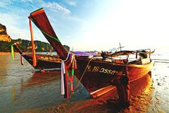 Fisherman are repairing and painting fishing boat or wooden boat with sunlight stock photo