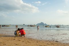 Children playing sand and some people walking and relaxing at Ao Nang beach before the sunset. KRABI THAILAND - 2 FEB 2018: Children playing sand and some people Stock Image