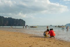 Children playing sand and some people walking and relaxing at Ao Nang beach before the sunset. KRABI THAILAND - 2 FEB 2018: Children playing sand and some people Royalty Free Stock Photos