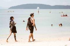 Krabi Thailand - Februari 12, 2019: En grabb och en flicka som täckas tungt med tatueringar, går på en tropisk sandig strand tatu royaltyfria foton