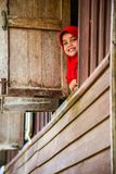 Cute muslim girl wearing red hijap smiling. Krabi, Thailand - May 2, 2015: Cute muslim girl wearing red hijap moving out of wooden windows smiling to visitors in Stock Images